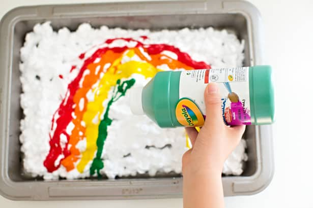 Pouring paint in a shallow pan filled with shaving cream to make rainbow shaving cream