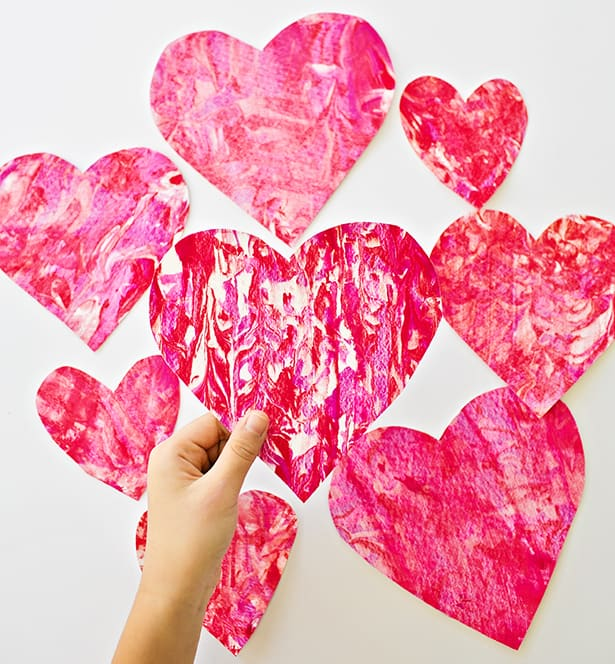 we love using shaving cream to make pretty marbled art prints we tried it with rainbow colors and thought itd be fun to make a valentines day version