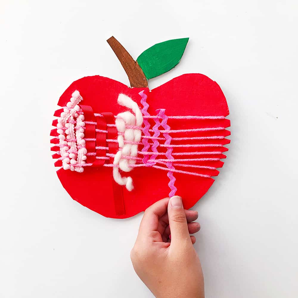 Ring in fall with an artful cardboard apple weaving craft for kids! A wonderful arts and crafts activity and fine motor skill practice.