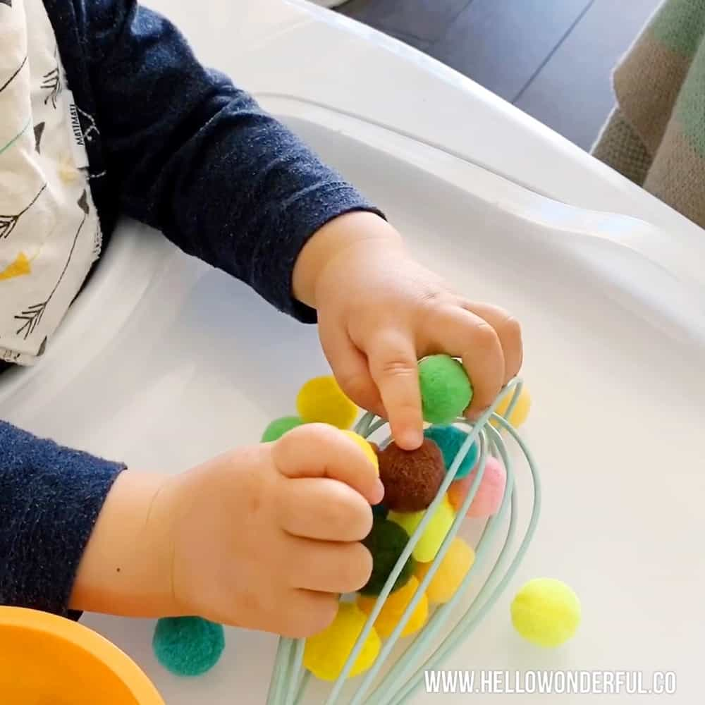 Baby playing with pom poms and kitchen whisk to practice fine motor and sensory skills.