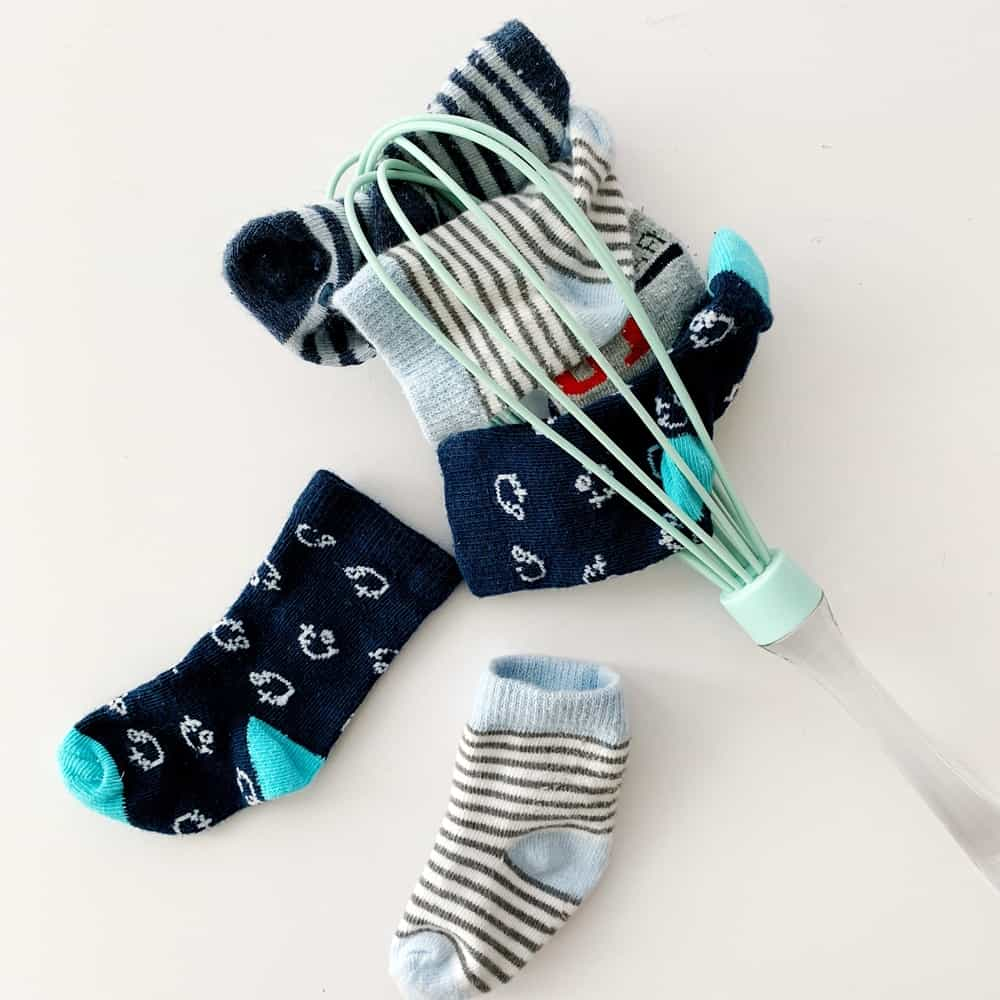Sock and whisk baby fine motor skills sensory activity.