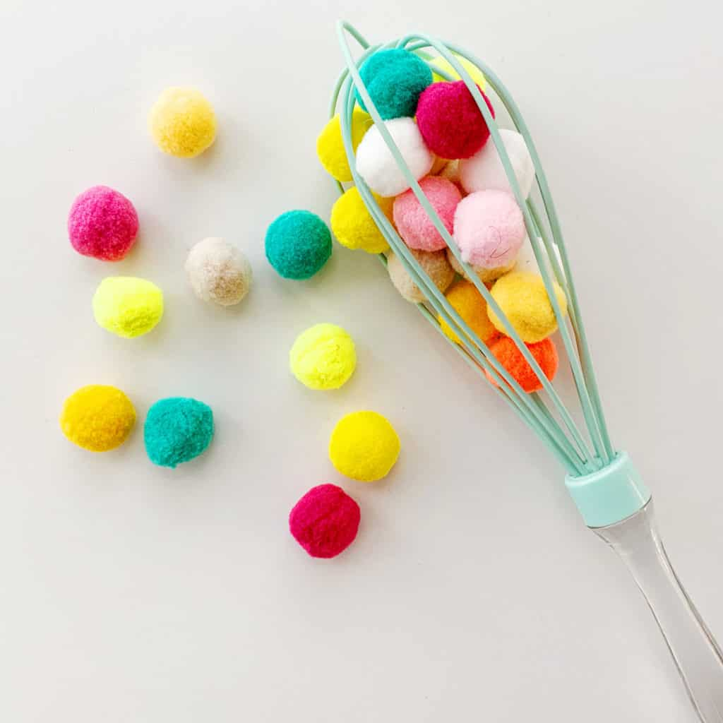 Pom poms and kitchen whisk activity to practice fine motor and sensory skills.