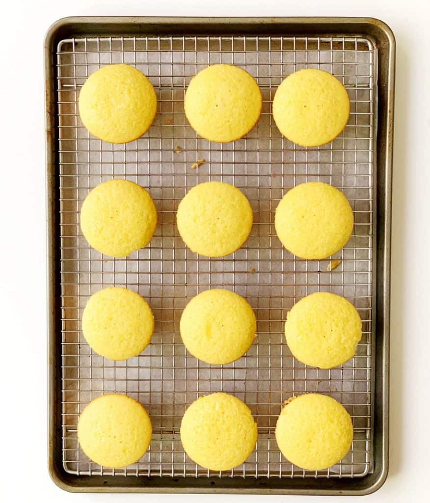 vanilla cupcakes cooling on a baking rack