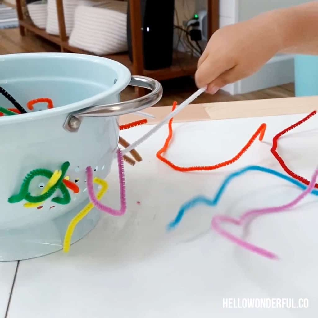 toddler grabbing pipe cleaners in colander to practice fine motor skills