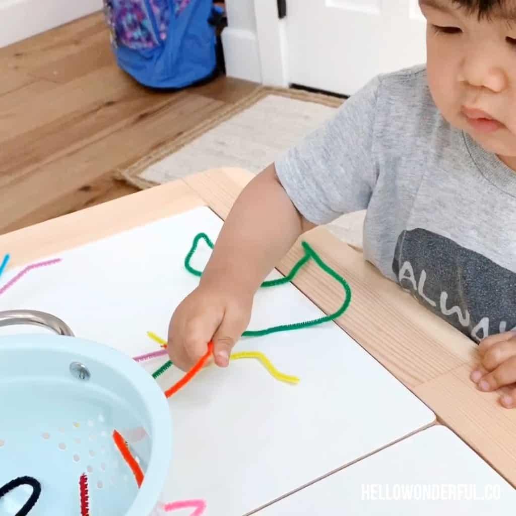 toddler grabbing pipe cleaners in colander for fine motor skills