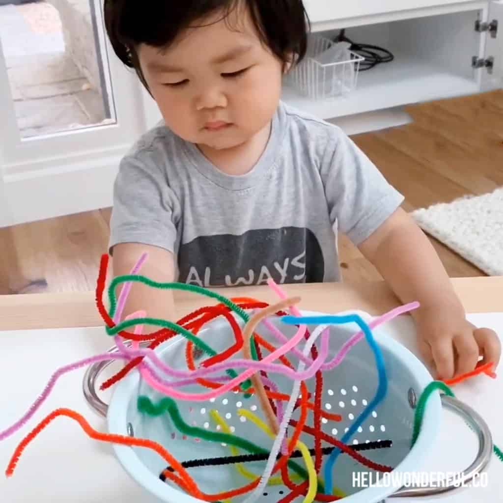Pipe cleaners in a colander for toddler fine motor skills