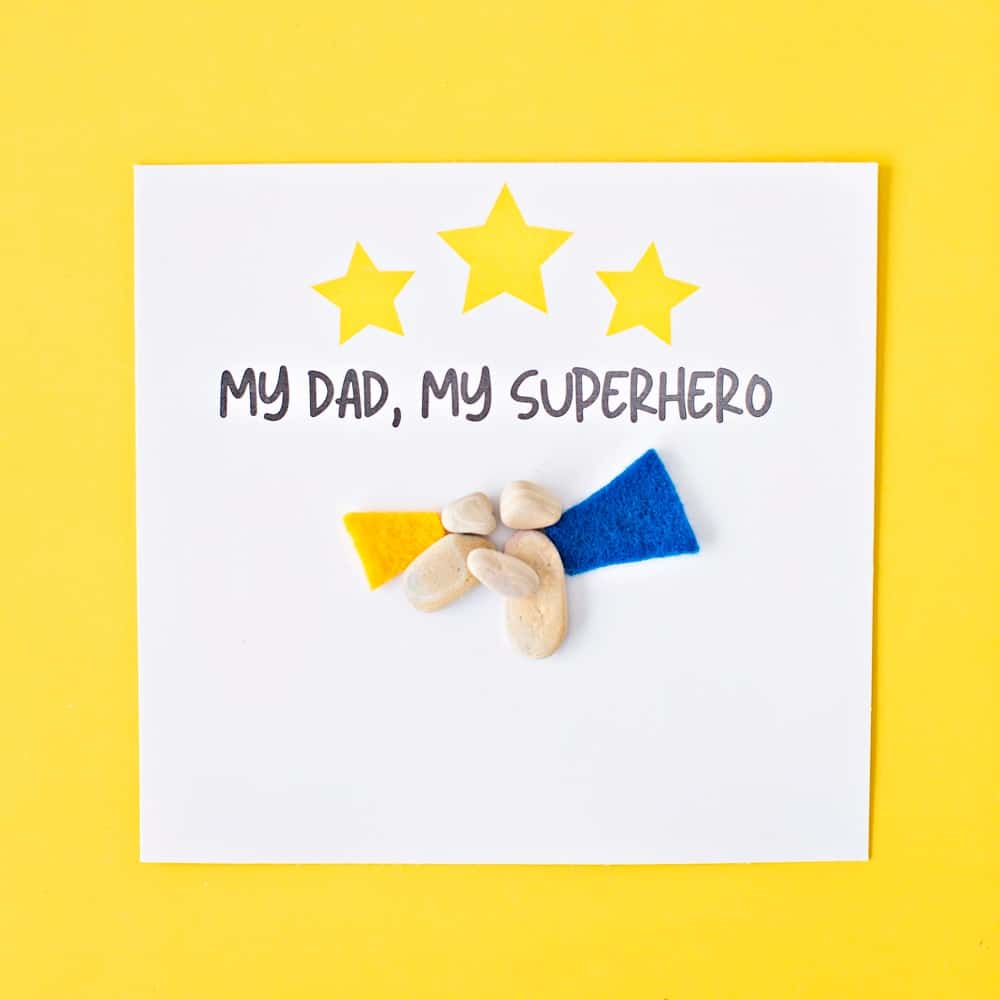 pebble rock art on yellow background for father's day that says My dad, my superhero
