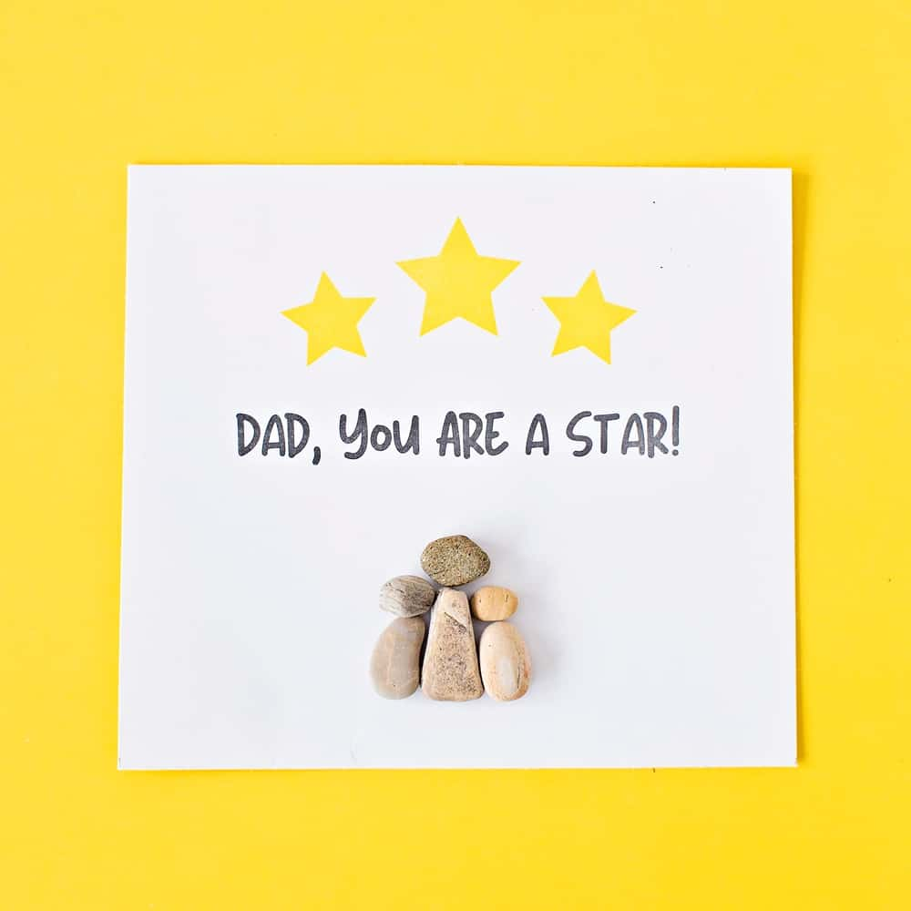 pebble rock art on yellow background for father's day that says dad you are a star