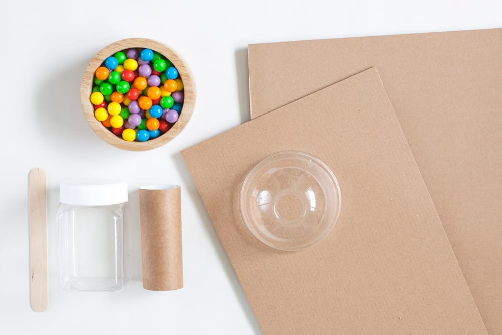 materials laid out to make a gumball machine showing cardboard, paper tube and candy