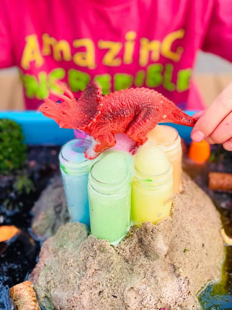 rainbow baking soda volcano science experiment for kids with toy dinosaur on top