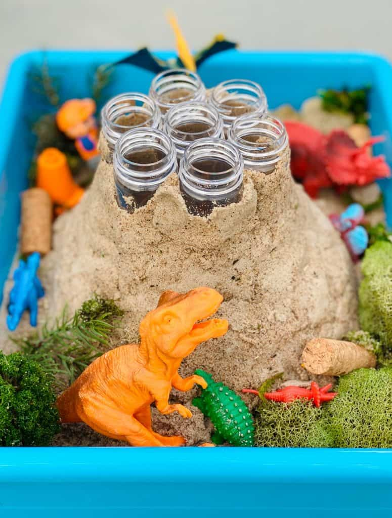 plastic test tubes around sand forming a volcano