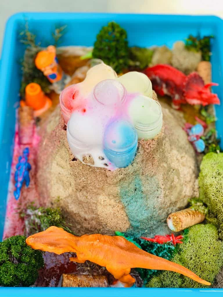 rainbow baking soda volcano science experiment for kids with toy dinosaurs
