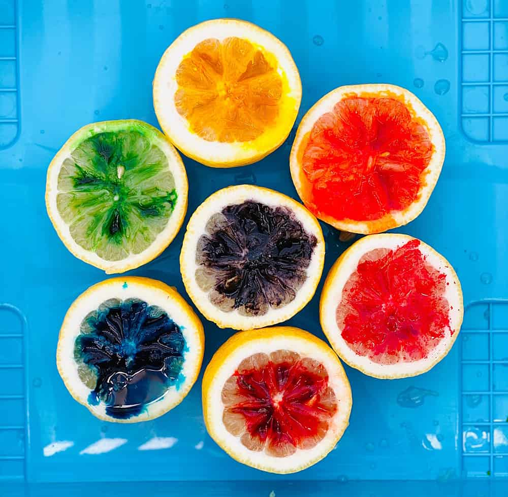 cut lemons in half with food coloring over them in rainbow colors