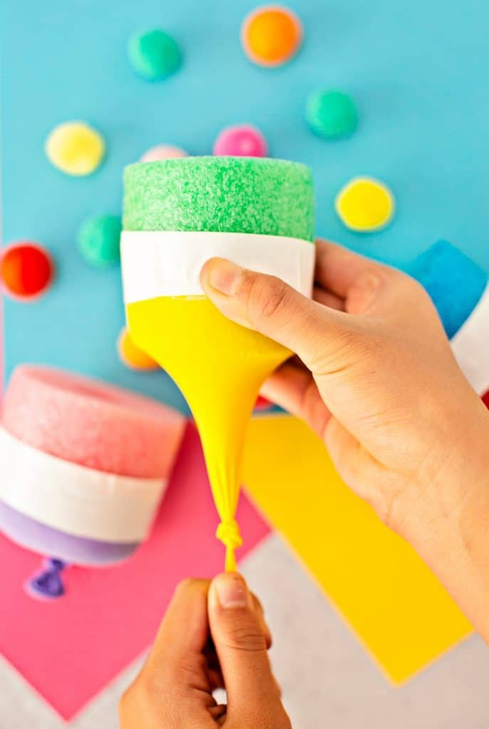 hand stretching balloon on a pool noodle pom pom shooter