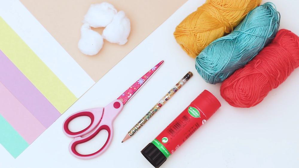 materials for paper ice cream craft like yarn, paper, cotton balls, scissors, glue