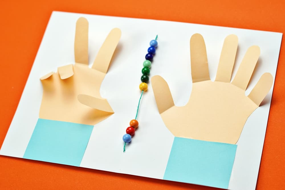 early math learning with paper hands cut out and counting beads