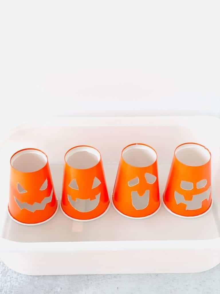 Orange paper cups cut into jack o' lantern faces for baking soda vinegar experiment.
